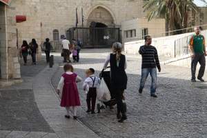 A religious Jewish mother walks with her children through the Armenian Quarter to the Jewish Quarter to celebrate Simchat Torah.