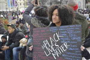 Washington D.C., USA - December 13, 2014: A young woman holds a sign at the protest march in Washington DC to bring attention to the recent shooting deaths of several unarmed black men by police.