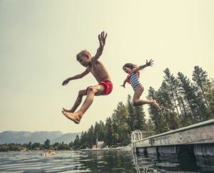 Kids jumping off the dock into a beautiful mountain lake