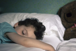 Young-child-sleeping-in-bed-with-teddy-in-background-000072859875_Medium