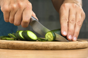 hands slicing cucumber on the cutting board