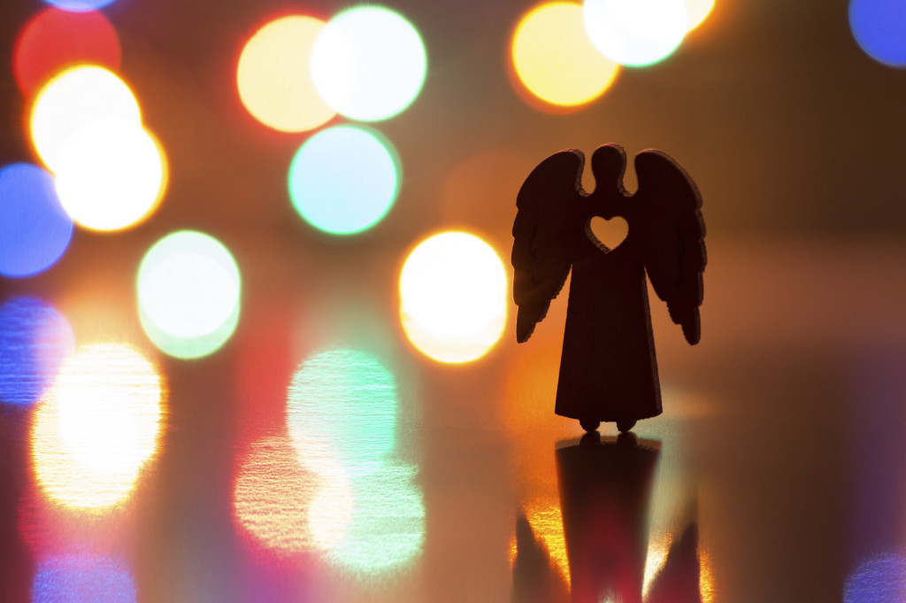 Silhouette of Christmas angel with hole in form of heart with ga